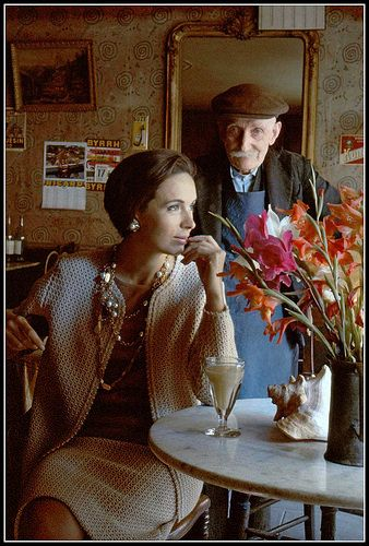 Marla in crocheted skirt and jacket worn over silk blouse sits in cafe de Sauxillanges, owned by M. Desandes (73) a Croix de Guerre recipient, photo by Frank Horvat, ELLE, 1960.