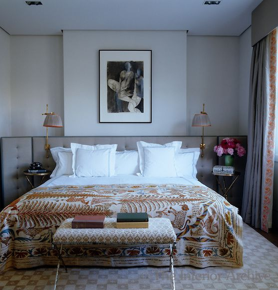 In the master bedroom a silk-upholstered headboard incorporates reading lights and a folding screen and the bed has a vintage cover