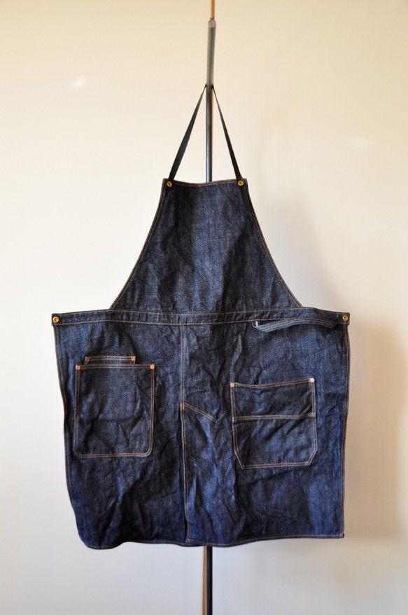 name_ denim aproncolor_ indigo bluematerial_ vintage selvedge Denimワンサイズで、平置きで全長88㎝、幅は腰の広い所で74㎝。革紐の穴の位置である程度サイズ調整可能です。サイズ感がわかりずらいと思いますので、気になる方は一度お問い合わせください。セルヴィッジデニムを使用、ドーナツボタンは真鍮製です。レザーの肩ひも、腰ひもは取り外し可能で洗濯も問題ありません。ポケット部分はリベットで補強。しっかりした厚手の生地なので、ハードな使用にも耐えそうです。受注製作となるため、ご注文のタイミングにより2週間〜4週間ほどお時間~をいただくことがございます。ご質問いただければ、大まかな納期をお知らせいたします。※以前にお気に入り登録されている方へ若干仕様変更しております(胸ポケット・リベット等)。ご注意ください。※返品・交換について現在、皆様に実物をご覧いただく機会が持てず、限られた画像のみでご判断いただいております。その為、未使用品に限り、お客様都合の返品または交換に応じます。(往復の送料は御負担いただきます。)