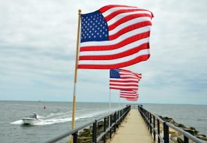 When is Memorial Day? Plan Ahead for the Unofficial Start of Summer: When Memorial Day weekend arrives, New England travelers head to the beach. Here, American flags fly proudly along the pier at Jennings Beach in Fairfield, Connecticut.