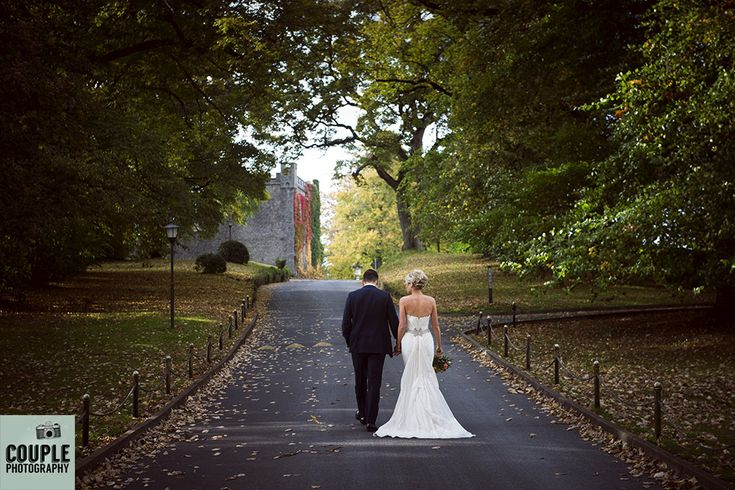 The bride & groom walk through the colourful autumn leaves in the driveway of Durrow. Weddings at Durrow Castle photographed by Couple Photography.