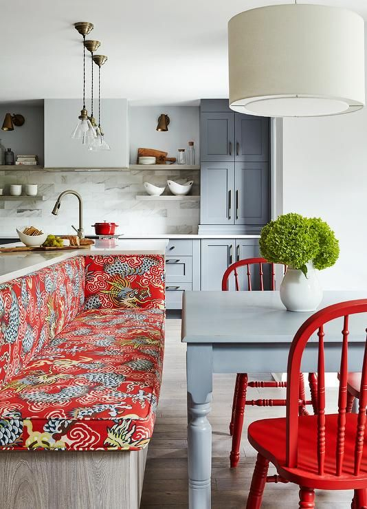 Contemporary eat-in kitchen features a built-in dining bench fixed to the back of a gray oak island and topped with red dragon print bench cushions facing a gray farmhouse table seating two red dining chairs lit by a white drum pendant.