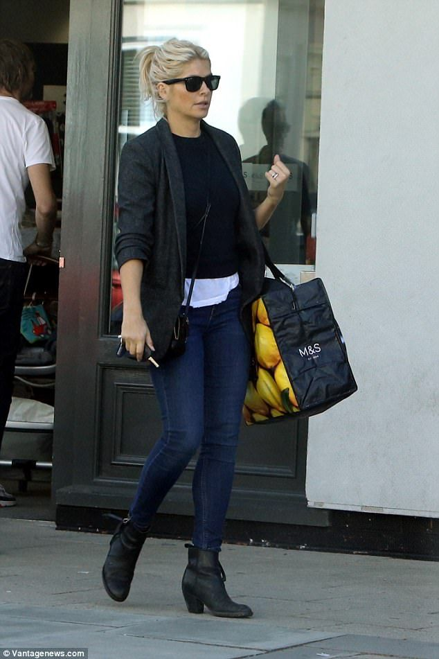 Casually clad: The bubbly TV star clad her sensational curves in a clingy black jumper, wh...