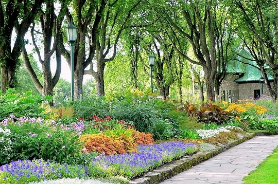 Jardins Jeanne-d'Arc, Québec  Créé en 1938 par l'architecte paysagiste Louis Perron, ce jardin revêt un style bien particulier. De forme rectangulaire et légèrement en contrebas, il allie le style classique français aux plates-bandes mixtes à l'anglaise. On peut y admirer plus de 150 espèces : des fleurs annuelles, des bulbeuses, mais surtout des plantes vivaces. La floraison, s'échelonnant d'avril à octobre, donne couleurs et parfums qui enchantent les visiteurs tout au long de la saison.