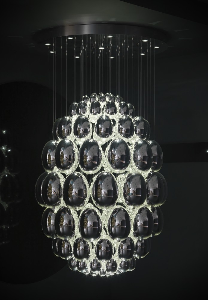 """Lit glass egg sculpture / Lasvit's Ronny Plesl has designed """"Uovo d'argento"""" and """"Uovo d'oro"""", a suspended lamp made of 124 handblown glass eggs. A thin wire suspends the eggs from the ceiling and gives the entire structure a long oval shape - a larger egg made by smaller eggs, lit from inside."""