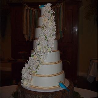 7 tier buttercream wedding cake with gumpaste flowers and birds.