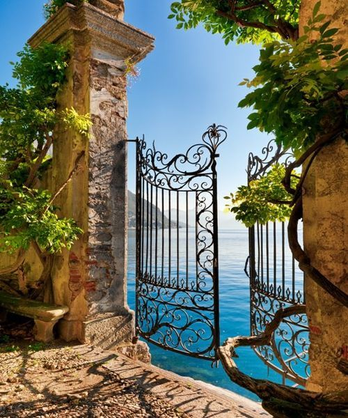 Ornate iron gate set into ancient wall opening onto the water. Lake Como, Italy. Photographer John Scanlan www.scanlan.com