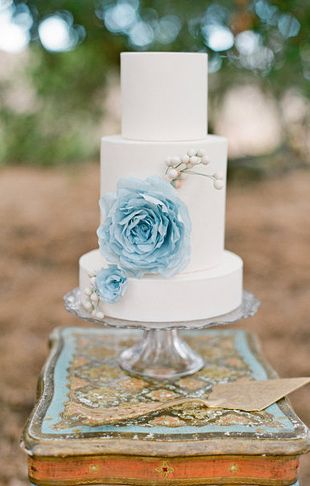 White 3 tier cake with pale blue sugar flower