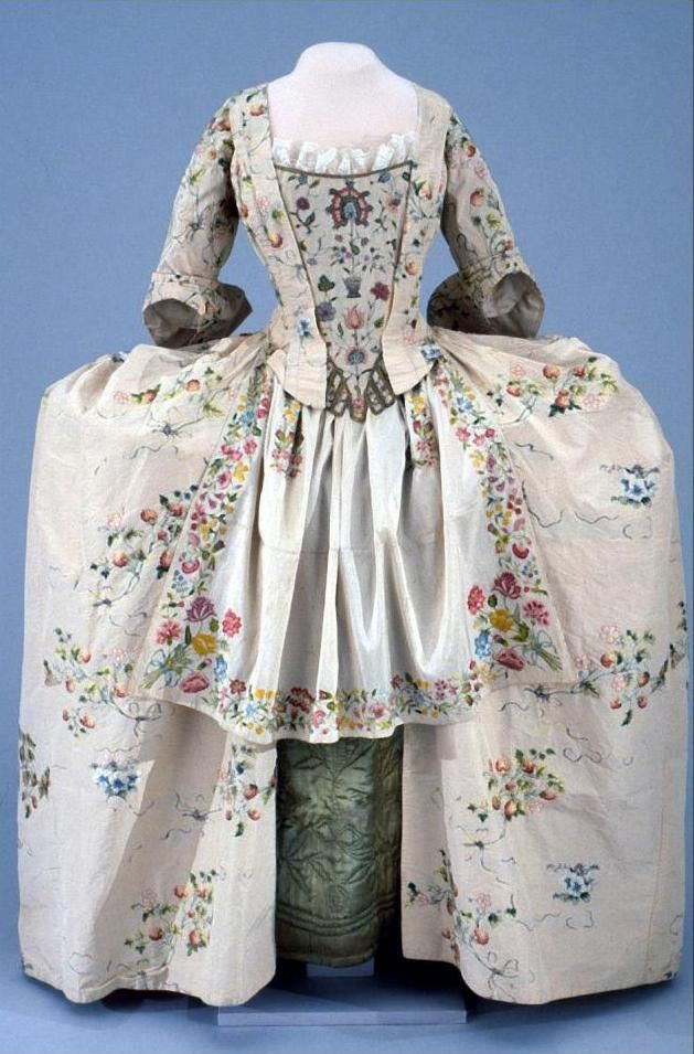 Robe a l'anglaise: ca. 1755 (with later alterations), English, Spitalfields silk, embroidery (including a profusion of strawberries), lined with linen, skirt and sleeve linings of silk. Made to accommodate wide panniers (missing), stomacher (missing) and petticoat (missing) (replaced in the photo with museum items). [Search for Acc. No. 1953-854]