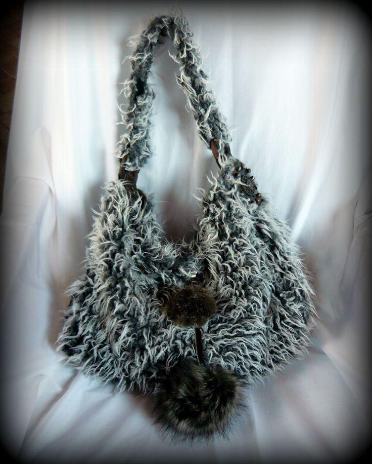 """Pom-pom-os """"Yeti"""" táska -handmade by Judy Majoros: Szürke-fehér műszőrméből készült a táska alapja, bélése bélésselyem. A táska elejét két sötétbarnás műszőrme pom-pom díszíti, ami csatos megoldása miatt levehető a táskáról, sőt többféle képen is kombinálható.Pántjai csatlakozására kívül és belül is kör alakú műbőr díszt készítettem. Pántja két sötétbarna fa karikával csatlakozik a táskához, és tépőzáras megoldása miatt állítható. Belseje díszített, és 4 zseb található benne."""