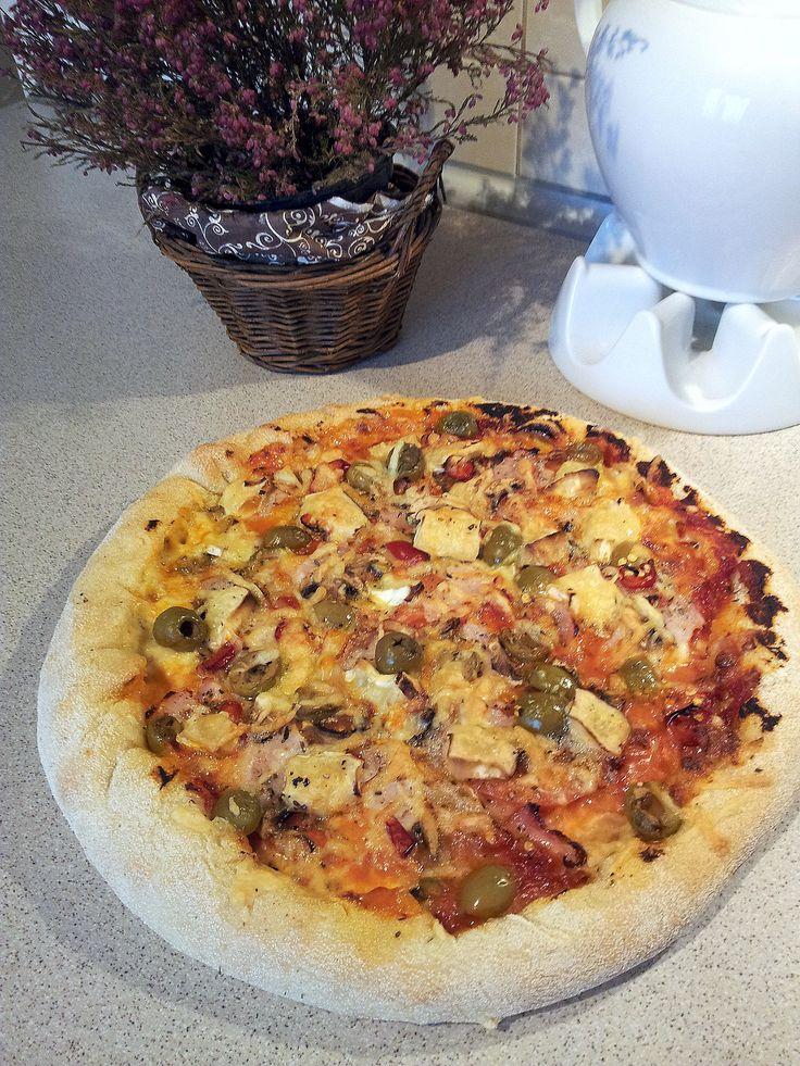 Pyszna pizza domowa na chrupiącym cieście. Dodatkami są ser mozzarella, ser brie, ser żółty, oliwki, pomidor, wędlina, papryczka peperoni czereśniowa.