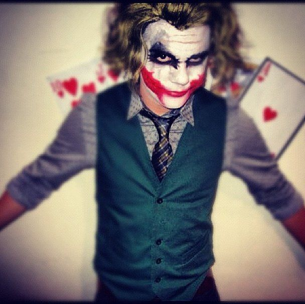 Use a movie still to copy the Joker's face with black, white, and red paint. Brush your hair out to look wild and wear a button-down shirt with a tie.