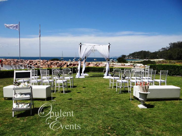Dark Bamboo, sheer white draping, tiffany chairs and elegant white ottomans - a romantic afternoon wedding ceremony on Glover Lawn, The Anchorage, Port Stephens.