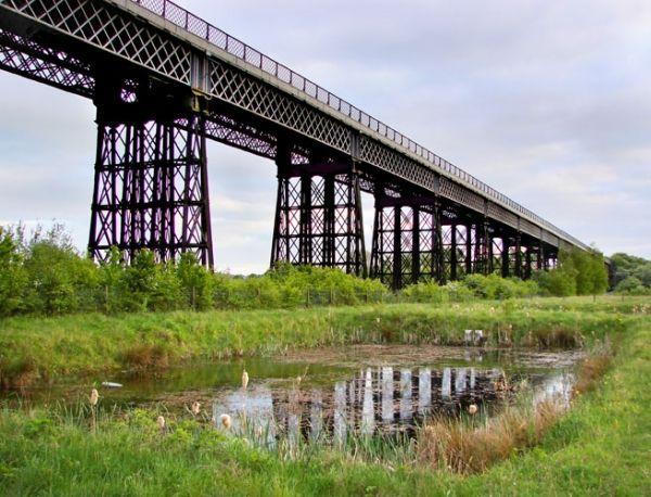 Bennerley Viaduct est un pont ferroviaire (pont-rail), pont en poutre en treillis avec tablier supérieur et pont en fer qui a été construit de 1876 à 1877. Le projet est situé à/en Nottinghamshire et Derbyshire, East Midlands, Angleterre, Royaume-Uni, Europe.