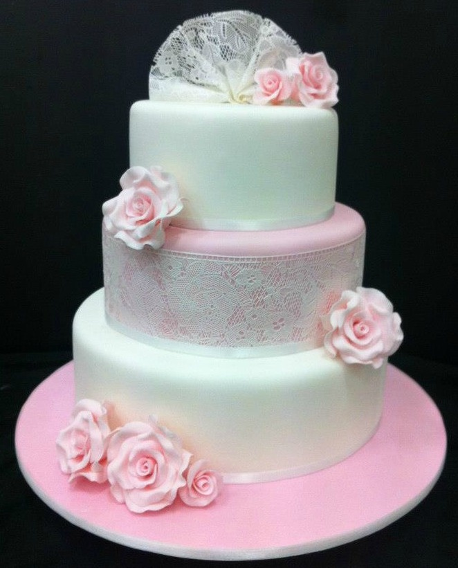 This wedding cake features the delicate edible sugar veil lace on the middle tier and lace fan on top tier. All pink sugar roses are edible as well.