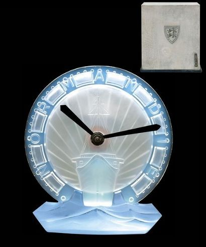 """Lalique's collaboration with Art Deco clockmaker ATO: This piece's design is made from blue glass, blown and molded to resemble the bow of the ship against a backdrop of sunshine alongside the word """"Normandy."""" Normandy refers to SS Normandy. She entered service in 1935 as the largest and fastest passenger ship afloat; she is still the most powerful steam turbo-electric-propelled passenger ship ever built."""