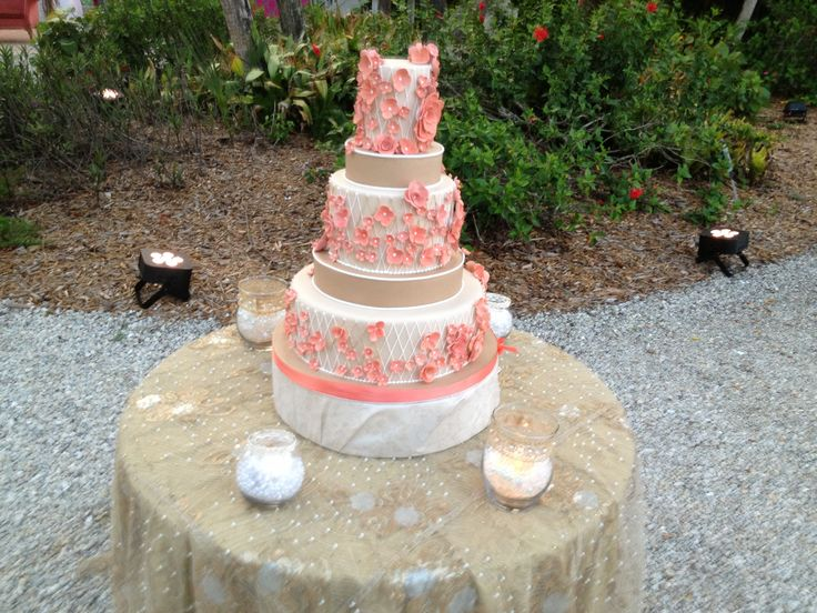 Tan fondant wedding cake with white lace and peach flowers