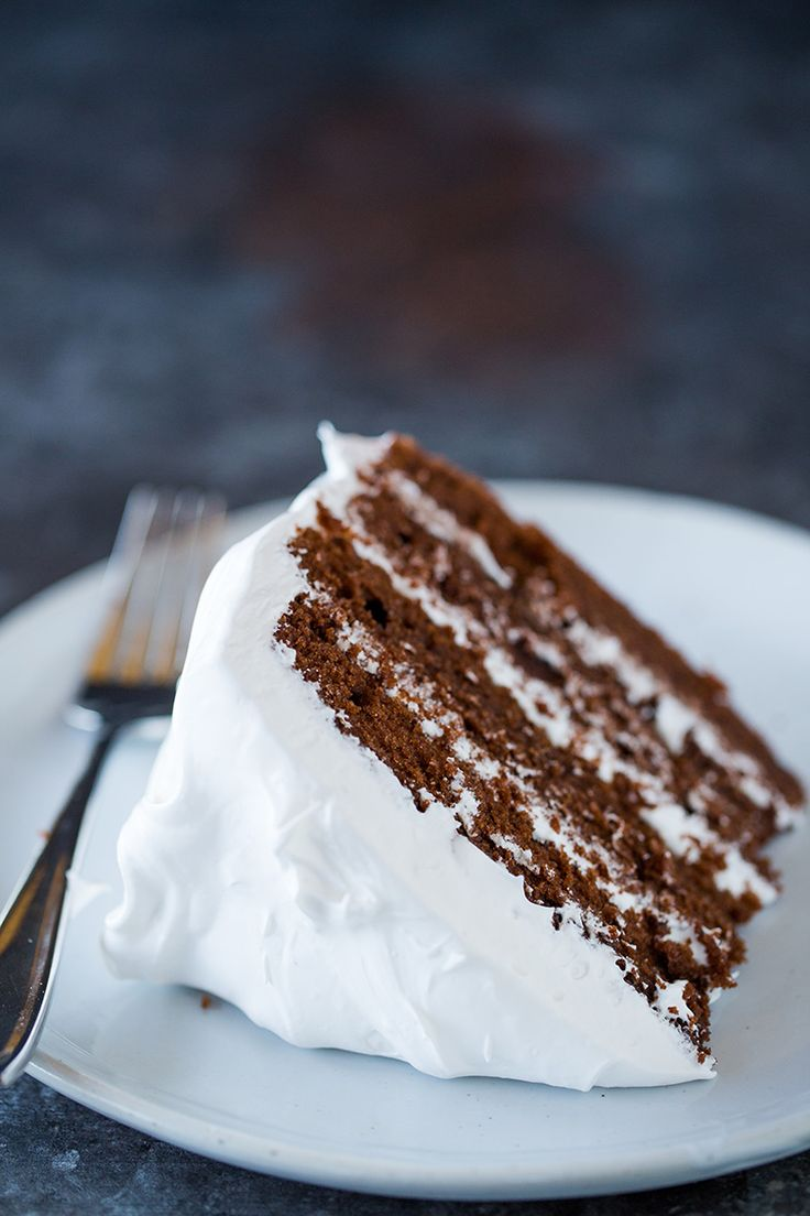 A slice of four-layer devil's food cake on a plate with a fork.