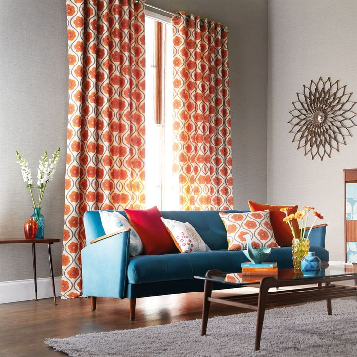 オレンジの花がポップでキュートなカーテンにブルーのソファの組み合わせ。オレンジと青って相性がいいんですね!参考になります。