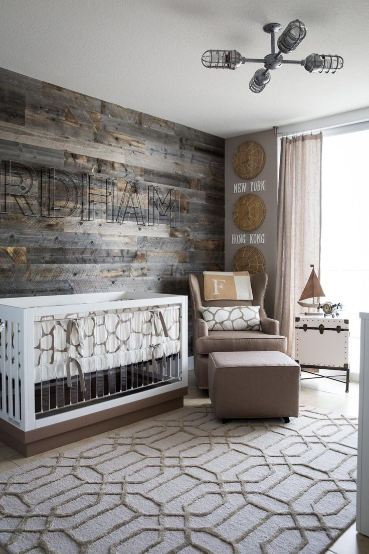 This subtle travel-themed nursery features a driftwood wall fused with modern details like an acrylic crib to create the perfect modern meets rustic baby room that's serene and inviting.