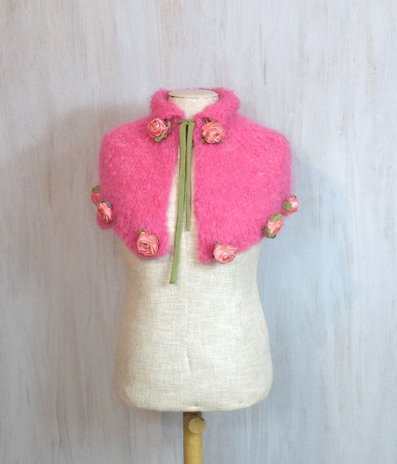 Unique crochet capelet decorated with pink textile roses. The capelet is knitted and the flowers are made by myself. Fantastic accessory for romantic style lovers!  The capelet is made of pinkmohair yarn. It is presented on my adult mannequin (small-medium size) but I recommend this item for girls or women of small build. Please check size (below).  The roping (with thin green textile rope) let you adjust width near neck.  You can wear this scarf over the outerwear or over her everyday…