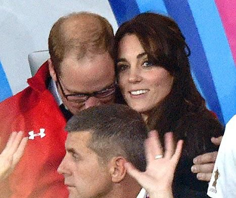 William gives his wife a cuddle while they watch Rugby match