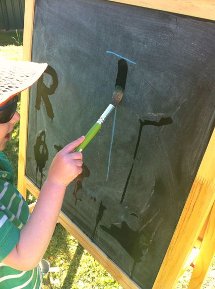 painting with water on chalkboard tracing letters