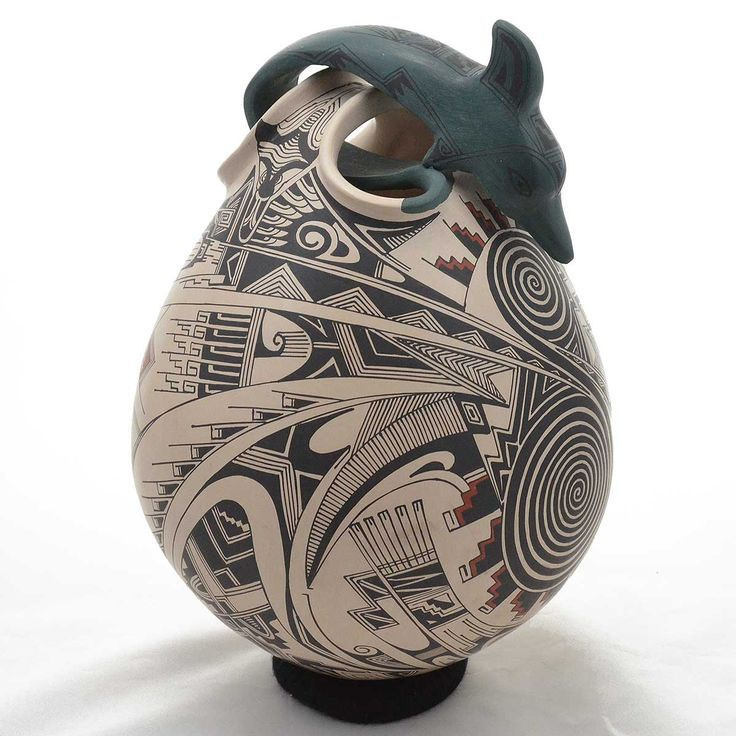 """Manuel Rodriguez, prolific potter, has always been a favorite with true collectors. His elaborate motifs are never copied, by a village of known """"design thieves."""" His themes are just too difficult to copy---and the other artists prefer something simpler. This dolphin is extraordinary leaping out of"""