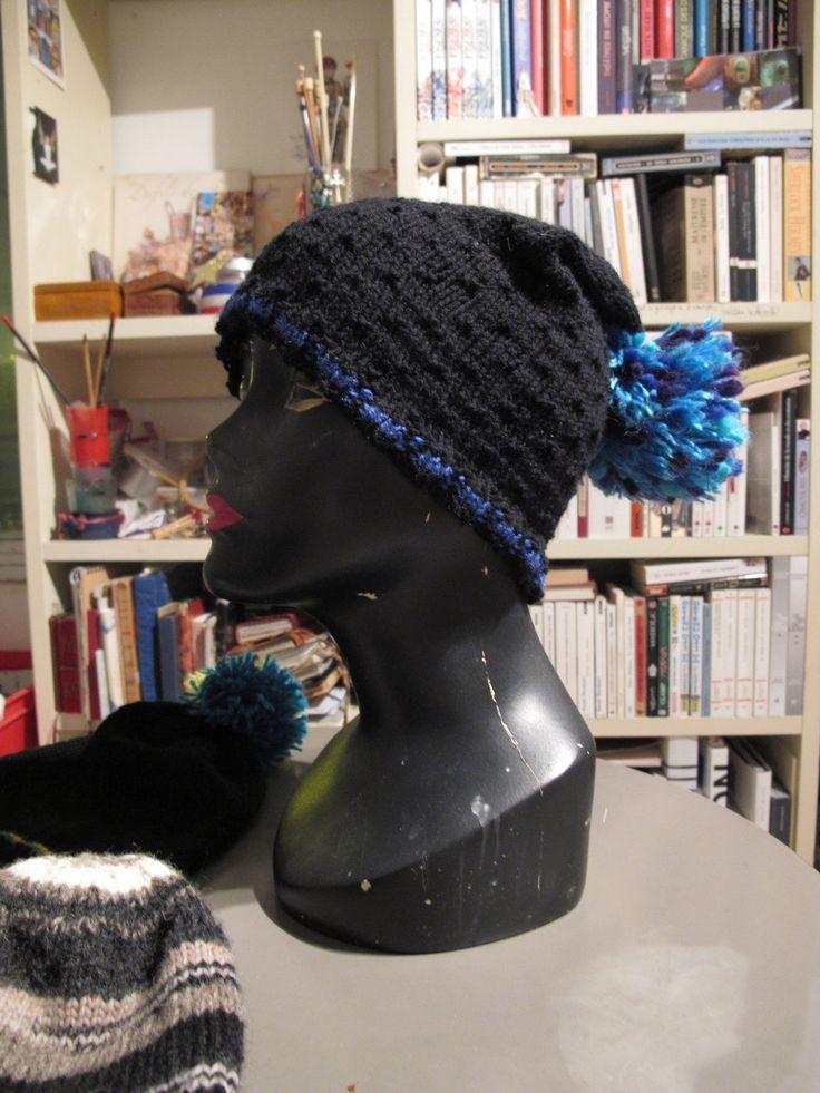 """Bonnet slouchy noir en semis piqu¨¦, avec un pompon bleu by The Soft Needle Ce bonnet est de forme """"slouchy"""", de fa?on ¨¤ ¨ºtre un peu rabattu sur l'arri¨¨re de la t¨ºte, et comporte un volumineux pompon violet, bleu et turquoise. Sans ¨¦tirement, le tour de ce bonnet est de 47 cm. Il peut s'¨¦tirer facilement jusqu'¨¤ 50-55 cm. C'est une taille un peu plus large que la moyenne... Mais qui sera d'autant plus couvrante si vous avez un tour de t¨ºte qui correspond ¨¤ cette moyenne. La laine…"""