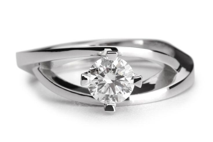 Een sierlijke verlovingsring waarbij twee banden om de diamant heen krullen en uiteindelijk in elkaar versmelten. De diamant is gevat in een chaton die boven de ring uitsteekt. De verlovingsring Saint Julians is uit te voeren met een diamant formaat naar keuze.