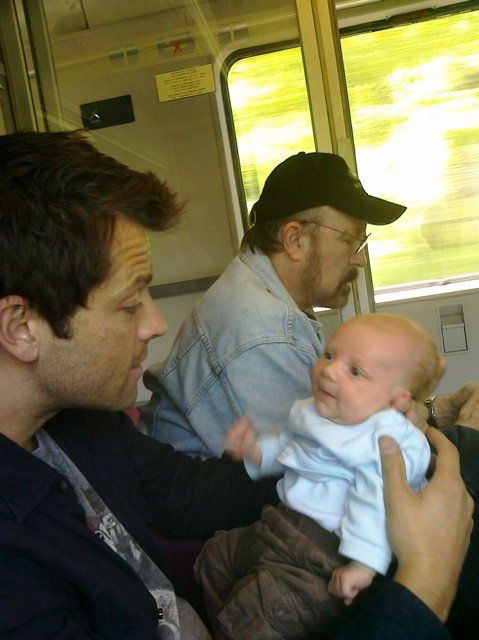 Misha, baby West, and Jim Beaver in the background somehow oblivious to all that cuteness.