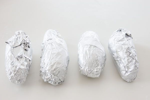 Wrap the potatoes in foil and bake in a 350 degree F (170 C) oven until a toothpick easily passes through (about 40-50 minutes).