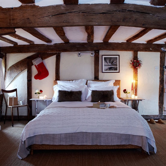 Step inside a cottage dressed for Christmas: Christmas bedroom:   The beautiful exposed beams in this bedroom give it such a cosy feel. A rattan headboard adds to the rustic charm, along with pretty bedlinen and fluffy brown pillows. A stocking and wreath hang either side of the bed for a subtle Christmas touch. Get the look:   The bed and the table (painted in Farrow & Ball's Smoked Trout) came from Habitat and the bedlinen from Costco. The stockings are from Retreat Home and flooring is…