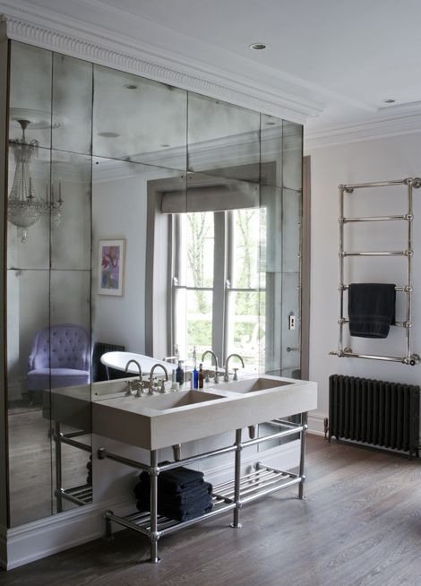 Antiqued mirror glass panelling in a Primrose Hill Townhouse bathroom. The outer panels are antiqued to a medium effect, leaving the inner panels clear to be used as a normal mirror. The outer edges of the panels are finished with a patinated bronze trim