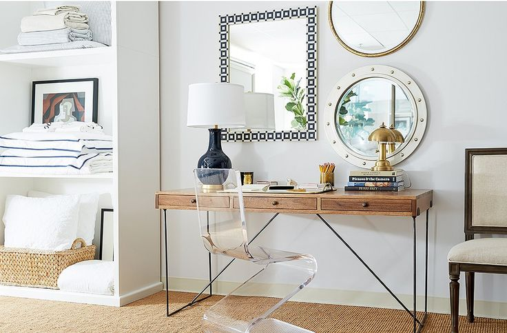 A desk vignette combines an eclectic mix of designs—an acrylic chair, a steel-and-wood desk, table lamps in glazed navy and gleaming gold, and a trio of mirrors in exotic materials.