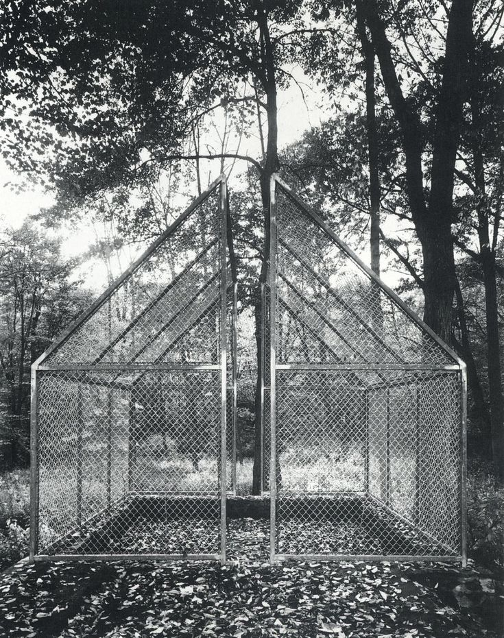 """Philip Johnson, Ghost House, (1984) This enclosure located on the grounds of the Glass Hous is built in the shape of a gabled house, but made of chain link and steel. The structure is a tribute to Johnson's friend, the architects Frank Gehry, who elevated chainlink fencing ti the status of avant-garde architecture. The function of this 16.5 x 21 foot """"house"""" was to protect the flower garden located within from roaming deer.It is split down the middle and rests on an old foundation left from…"""