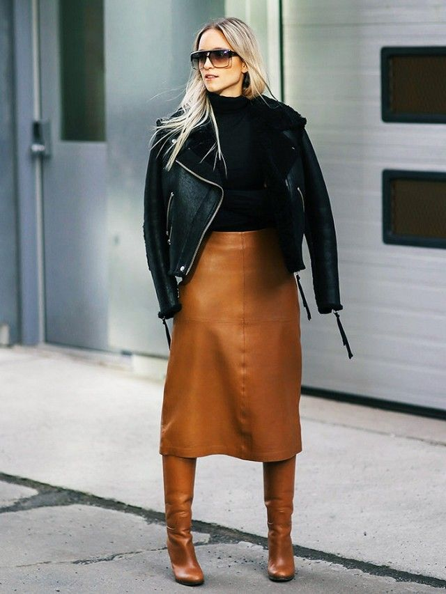 Charlotte Groeneveld wearing a black shearling jacket with a tan leather skirt and tan leather boots, with a black roll neck.