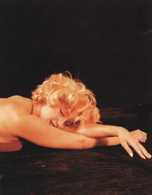 Marilyn. Red dress sitting. Photo by Milton Greene, 1957.