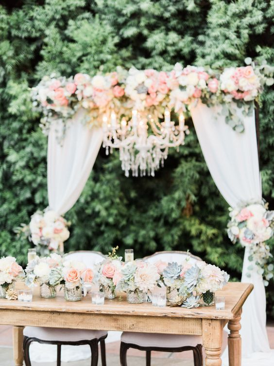 Wedding arch with fabric and chandelier. Sweetheart Table flowers