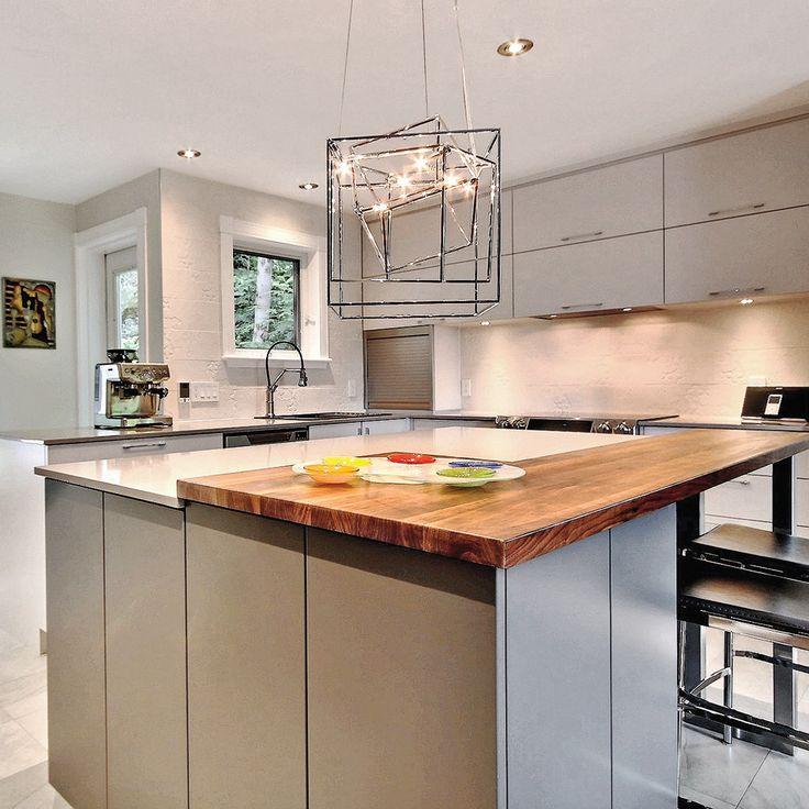 L'élimination d'une cloison a permis d'ouvrir la cuisine sur le salon, ce qui agrandit concrètement la pièce. Mais l'impression d'amplitude tient aussi à l'exploitation de couleurs neutres et claires qui repoussent les limites spatiales. Les surfaces en thermoplastique des modules oscillant entre le gris pâle et le gris foncé créent un doux contraste. Le quartz gris des comptoirs rappelant le béton ciré de même que la céramique à effet marbré au sol et façon crépi imma...