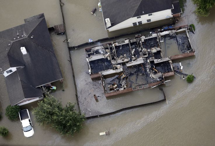 The flooding engulfed downed wires and caused fires in some buildings. This burned home in Spring, Texas, is surrounded by water.