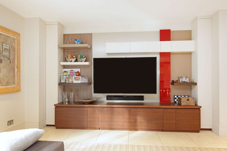 Television cabinet in various finishes including red colour-backed glass. The base section incorporates two large boxes on castors which hold children's toys by Andrew Manning Furniture