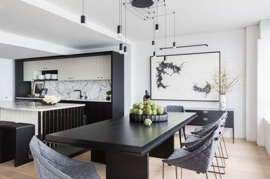The updated kitchen's principal colors—black, gray, and both Super White and Penthouse by Benjamin Moore—carry over into the dining area via quilted wool chairs and a custom table and benches | archdigest.com