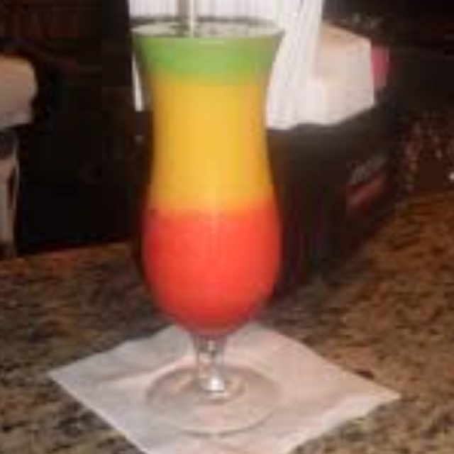 Bob Marley.  Red: 1 oz. lt. rum, 4 oz strawberry daiquiri mix, cup ice. Blend. Pour in bottom of glass. Yellow: 1oz. light rum, 3 oz chopped mango, 1 &1/2 oz sweet and sour mix, cup ice. Blend. Pour half into glass. Green: Add 1/2 oz blue curacao to remainder of yellow mix to make the green. Pour into glass. Top with orange curacao