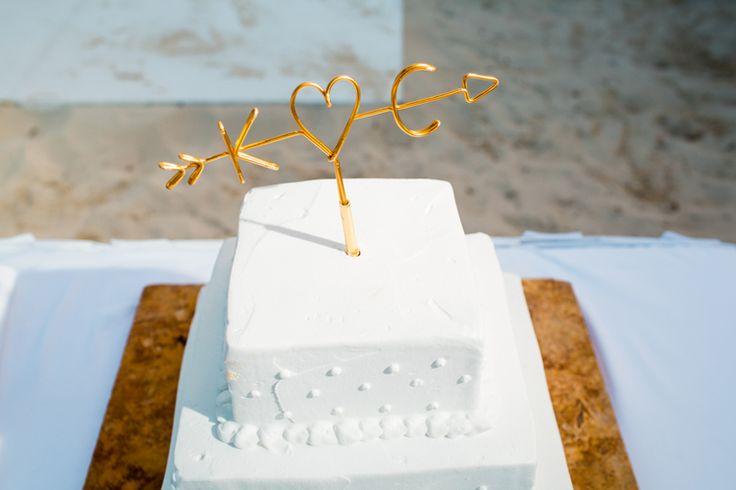 Destination wedding cake topper with arrow through heart and the couple's monogram (Jonathan Cossu Photographer)