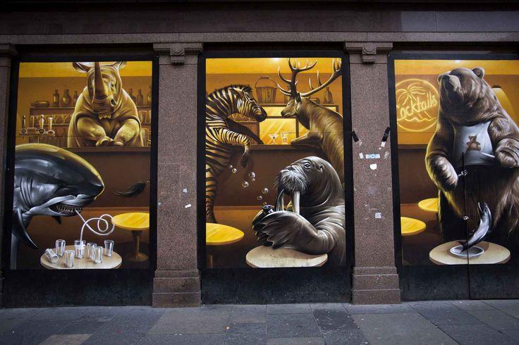 Argyle street café, Argyle streetSavoir sans cesse se réinventer est un challenge pour tout artiste. Défi relevé pour Smug, qui a réinterprété sa propre œuvre, l'Argyle Street café, en la recouvrant par une autre fresque. Là où l'image représentait dans des tons chauds la clientèle typique d'un café, elle fait aujourd'hui débarquer les habitants d'un zoo sur les tabourets de bar. Le style et les couleurs sont reconnaissables, mais l'artiste a totalement repensé son travail avec une pointe…