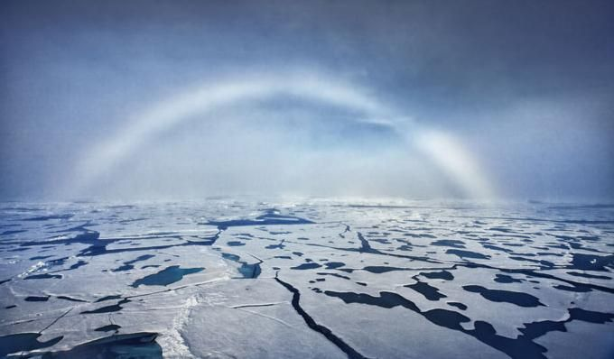"""WHITE rainbow streaks across the arctic sky. The rare phenomenon - named a fog bow - was spotted during a recent expedition to the North Pole.  A fog bow is a similar phenomenon to a rainbow, however, as its name suggests, it appears as a bow in fog rather than rain. Because of the very small size of water droplets that cause fog—smaller than 0.05 millimeters (0.0020 in)—the fog bow has only very weak colors, with a red outer edge and bluish inner."" Photographer Sam Dobson"