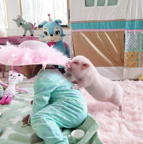 adorable little pig pulling little girl's hat