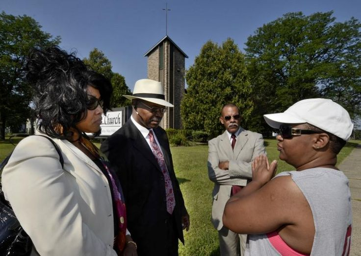 From left to right: Minister Paulette Camp, Elder Davis Camp Sr., and Elder Willart Tinsley Sr. of the Agape Apostolic Church converse with Roseann Plowden outside of the congregation's new worship space the former St. William's Roman Catholic Church, at the intersection of Project Road and Madison Avenue in Troy's Griswold Heights neighborhood on Wednesday. (Mike McMahon/The Record)