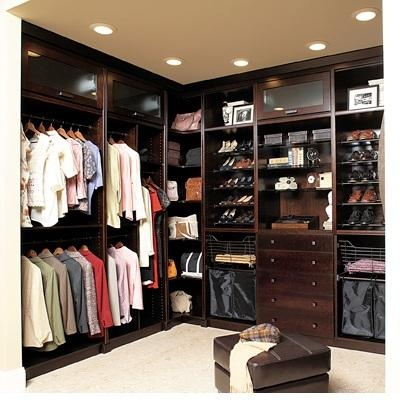 Closets made with dark wood can be over powering & claustrophobic.  If you are interested in this finish for your closet, make sure to have each section BACK LIT.  Corner storage is difficult to use unless it is made with glass & top lit. This dark corner will become a black hole for clutter & lost items. LOVE the glass upper storage for high end bags.  Be aware that doors & drawers add large dollars to your cost. LOVE: that the unit goes floor to ceiling (Closet Critque by…